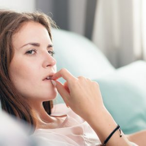 O fata care sta in pat si se gandeste daca sa foloseasca sau nu pilule contraceptive